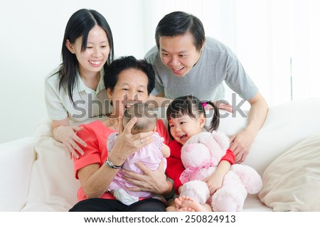 Asian three generations family looking at the new born baby. - stock photo