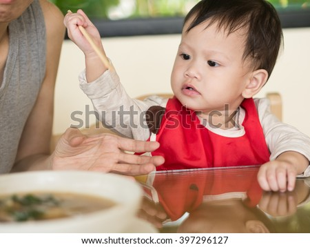 Asian toddler learn to eat meal herself holding chopsticks. - stock photo