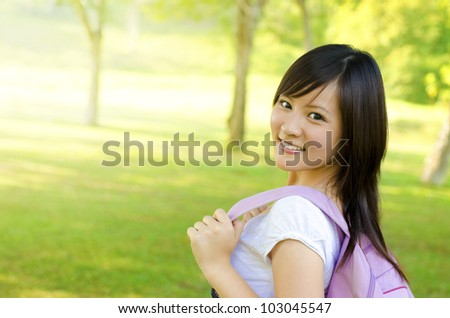 Asian university student walking on outside campus, green park - stock photo