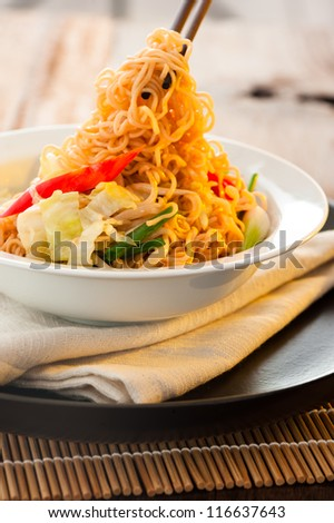 Asian vegetables noodles in white plate and chopsticks on wooden table as background - stock photo