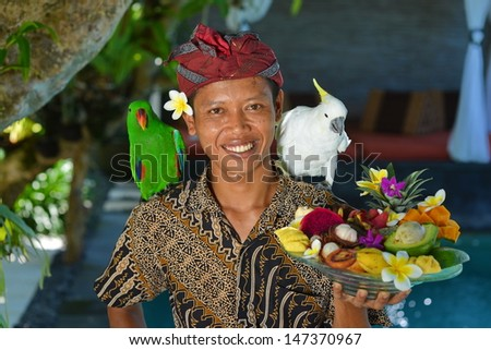 Asian waiter with a tray of tropical fruits in an exotic setting. Shoot in a luxury resort on Bali island, Indonesia - stock photo