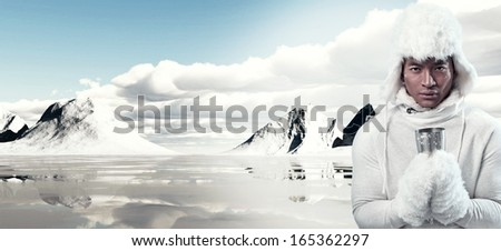 Asian winter fashion man in snow mountain landscape. Wearing white hoody sweater with furry hat and gloves. Holding metal mug. - stock photo