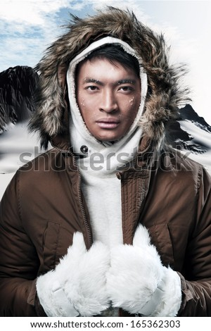 Asian winter sport fashion man in snow mountain landscape. Wearing brown jacket and fur hoody and white gloves. - stock photo