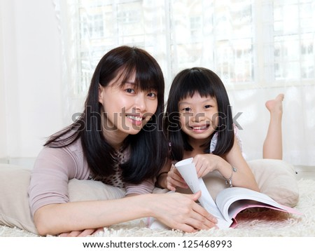 Asian woman and daughter lying on the floor and reading - stock photo