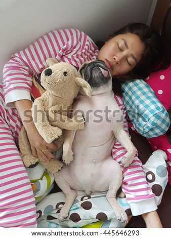 Asian Woman and her funny ugly pug dog sleep in the bed with doll. - stock photo