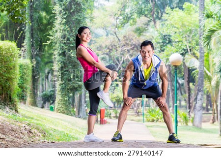 Asian woman and man, a couple, during gymnastics stretching for sport fitness in tropical park - stock photo