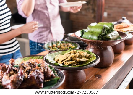 Asian woman and man choosing food at Indonesian buffet in restaurant - stock photo