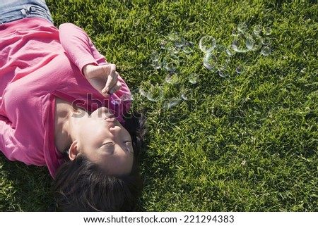 Asian woman blowing bubbles - stock photo