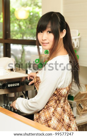 Asian woman brewing some coffee at the espresso machine in a coffee shop - stock photo
