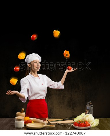 Asian woman chef juggling with vegetables, cooking skills - stock photo