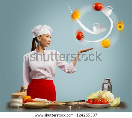 Asian woman chef juggling with vegetables in one hand, a collage - stock photo