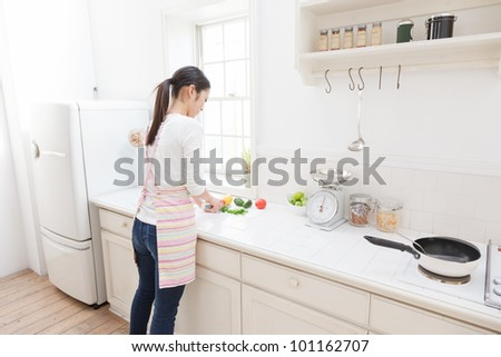 Asian woman cutting vegetables in the kitchen - stock photo