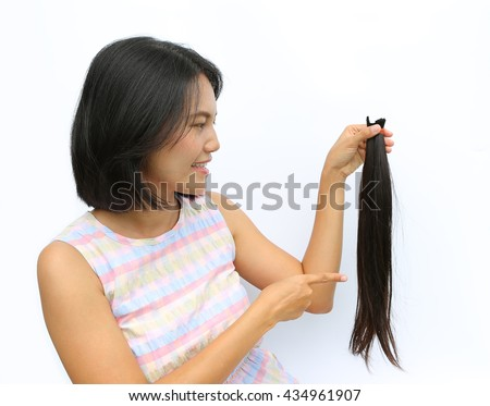Asian woman donating her hair to cancer patients - holding her former hair after a haircut, generously donating her long hair for making wigs for cancer patients who lost their hair - stock photo
