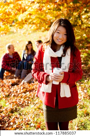 Asian woman drinking a warm drink in the fall - stock photo