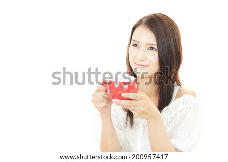 Asian woman drinking cup of coffee - stock photo