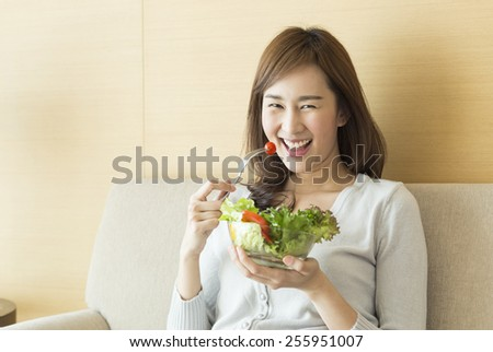 Asian woman eating healthy salad. - stock photo