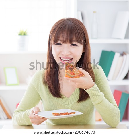 Asian woman eating pizza at home. Female living lifestyle indoors. - stock photo