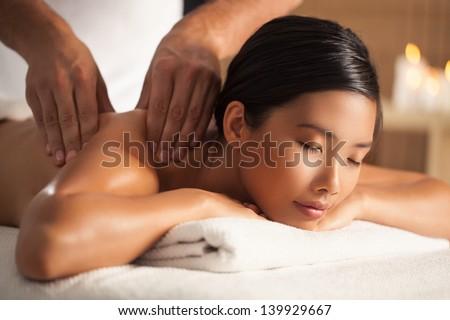 Asian woman enjoying a back massage. - stock photo