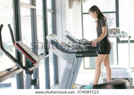 Asian woman exercising at the gym on a cross trainer, Woman training in a fitness club - stock photo