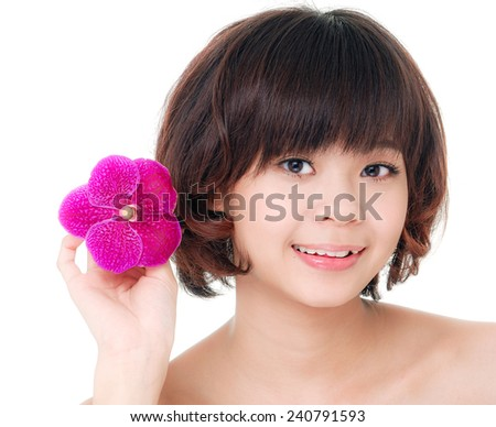 Asian woman face with clean skin holding orchid - stock photo