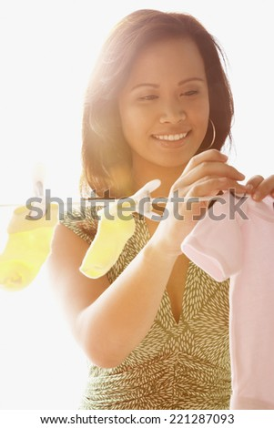 Asian woman hanging baby clothing on clothes line - stock photo