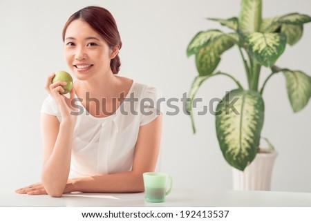 Asian woman having a green apple for breakfast - stock photo