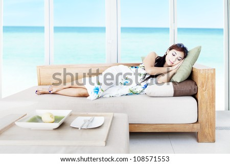 Asian woman having a sleep in the living room by the beach - stock photo
