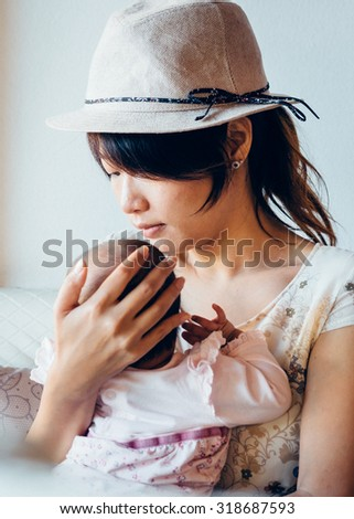 Asian woman hold tight her daughter, looks sad. Vintage retro style photo with color filters, vignette effect, and some fine film noise added. - stock photo