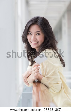 Asian woman holding a card in her hand - stock photo