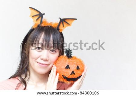 Asian woman holding a Halloween pumpkin - stock photo