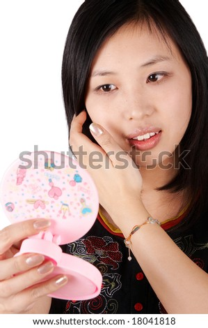 Asian woman holding a mirror and looking at it - stock photo