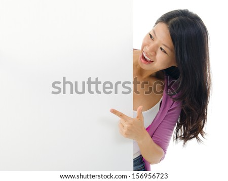 Asian woman holding and pointing to blank billboard. Portrait of young Asian female isolated on white background. - stock photo
