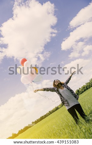 Asian woman holding balloons in the middle of every green. beautiful sky - stock photo