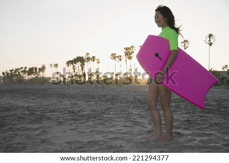 Asian woman holding boogie board - stock photo