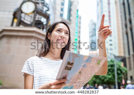 Asian woman holding city map and finger pointing up - stock photo