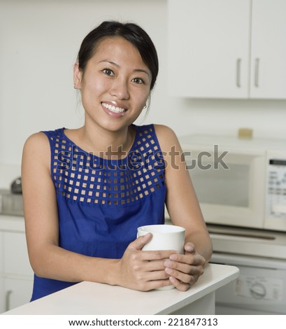 Asian woman holding coffee mug - stock photo