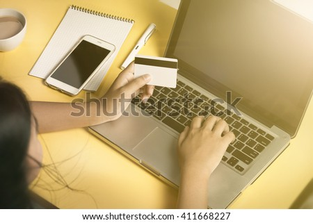 Asian woman holding credit card for shopping online on laptop display on working desk in office - stock photo