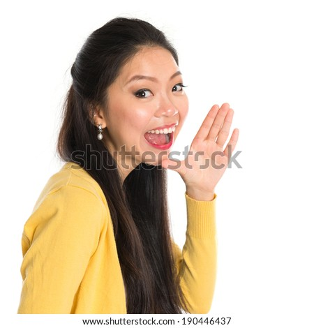Asian woman holding hand beside her cheek and shouts an announcement, isolated on white background - stock photo