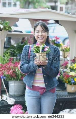 Asian woman holding potted plant - stock photo