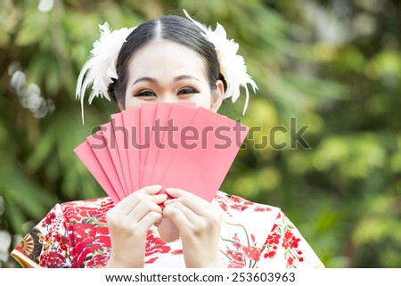 asian woman holding red bag for happy chinese new year - stock photo