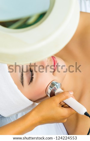 Asian Woman lies in a beauty spa getting a treatment with ultrasonic - stock photo