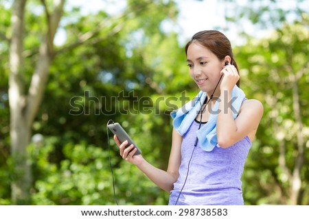 Asian Woman listen to music with cellphone - stock photo
