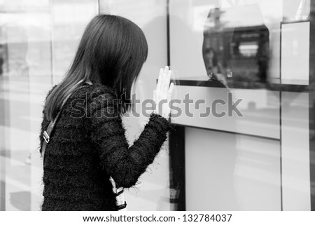 Asian woman looking at urban shop, black and white - stock photo