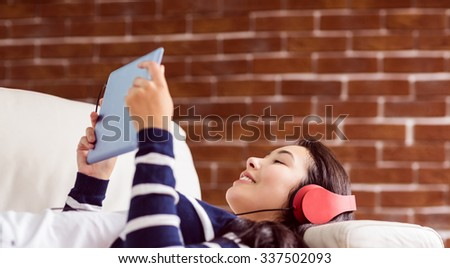 Asian woman lying on the couch listening to music at home in the living room - stock photo