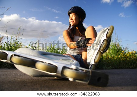 Asian woman on inline rollerblades enjoying a break. - stock photo
