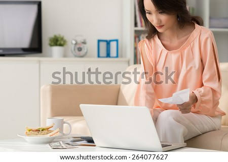 Asian woman paying her bills online - stock photo