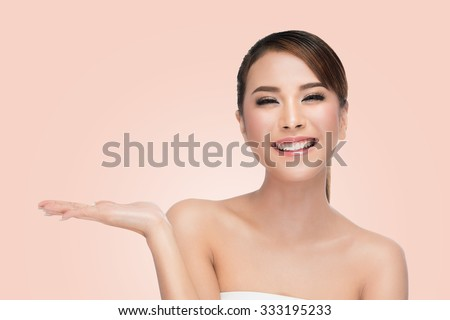 Asian Woman Portrait. Beautiful Spa Girl showing empty copy space on the open hand palm for text. Proposing a product. Skin Care Concept. on pink with clipping path - stock photo