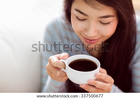 Asian woman relaxing on couch with coffee at home in the living room - stock photo