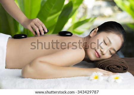 Asian woman relaxing with a spa treatment at the resort.The hot stones placed on her back. - stock photo