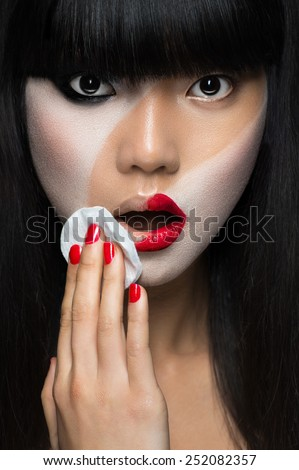 Asian woman removing make-up - stock photo